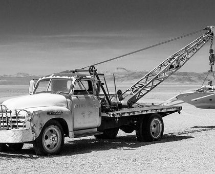 an old tow truck carrying an old flying saucer